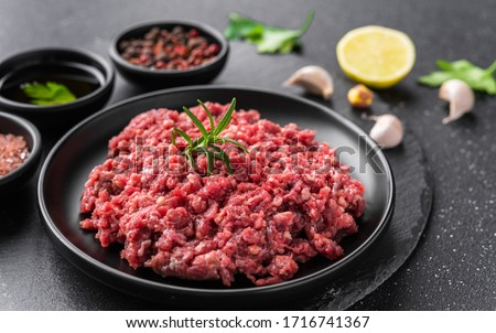 Fresh minced meat ground beef on a black plate against stone background Royalty-Free Stock Photo #1716741367