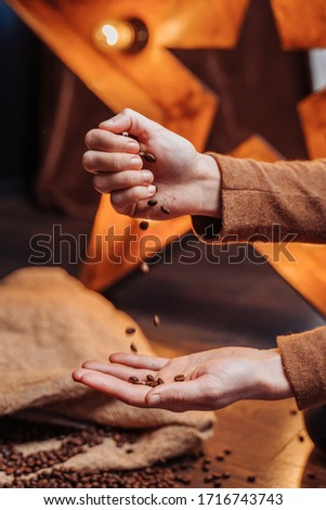 Closeup of the hand of a girl who pours out coffee beans to another hand. Coffee beans slowly fall. In the background lies a large bag with grains and there is a star shining with light bulbs #1716743743