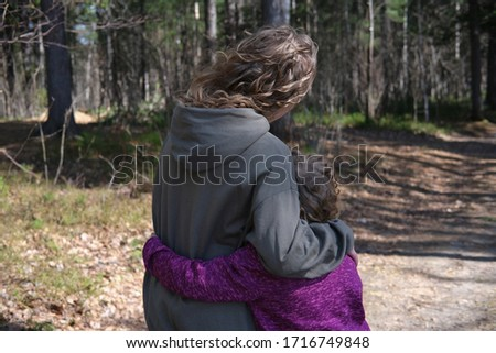curly sisters cuddling while walking in the forest. sisters hugging in the park on a sunny walking path. sisters love and support concept