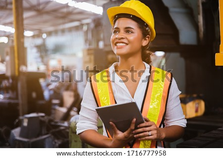 Industry maintenance engineer woman dark skin wearing uniform and safety helmet under inspection and checking production process on factory station by tablet. Industry, Engineer, construction concept. #1716777958