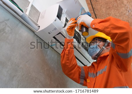 Mechanic wearing mask to prevent disease, Covid 19 Currently using electric drill to install air conditioner #1716781489