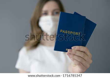 Young woman wearing a medical mask holds and shows a passport in a blue cover isolated over gray background, coronovirus, travel ban, forced deportation, unemployed, foreigner #1716785347