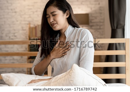 Portrait of 20s young Asian woman having difficulty breathing in bedroom at night. Shortness of breath, asthma, difficult to breathe problems. Corona Virus symptoms. Royalty-Free Stock Photo #1716789742