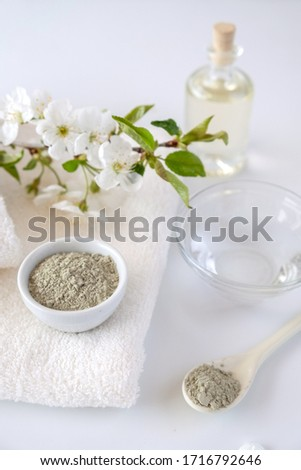 Ceramic bowl with green clay powder on white background. Ingredients for homemade facial and body mask or scrub and fresh sprig of flowering cherry . Spa and bodycare concept. #1716792646