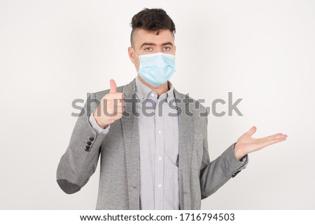 Young happy cheerful man wearing medical mask showing thumb up and pointing with the other hand while standing indoors. Good Job. Wearing casual clothes. #1716794503