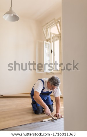 DIY, repair, building and home concept - senior man lying parquet floor board/laminate flooring (shallow DOF; color toned image) #1716811063