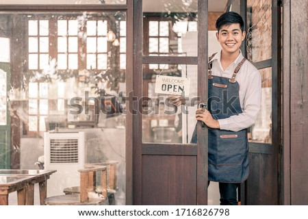 Store owner turning open sign broad through the door glass and ready to service. #1716826798
