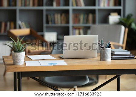 Wooden work desk with laptop and documents, books, modern interior of cozy cabinet, table for businessman or student at home, comfortable workspace, workplace with computer in apartment #1716833923