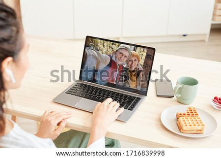 Unrecognizable young woman getting video call from her parents on laptop, sitting at desk at home #1716839998