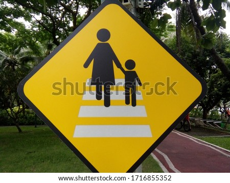 street sign warning to becareful about woman and children at the cross walk