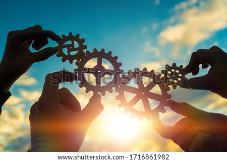 Four hands of businessmen connect gears to a puzzle on a background of sunset. Business concept idea, partnership, cooperation, teamwork, community, creative Royalty-Free Stock Photo #1716861982
