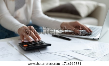 Close up of woman busy paying bills online on computer calculating household finances or taxes on machine, female manage home family expenditures, using calculator, make payment on laptop #1716917581
