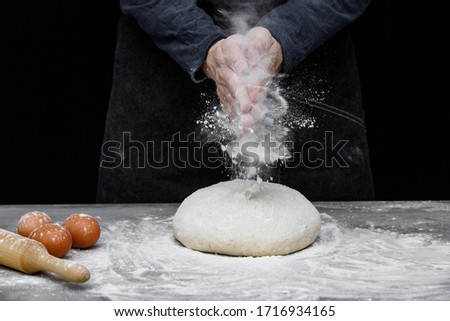 Thin male hands knead the dough for bread, pasta or pizza, close up. Closeup hand of chef baker kneading a dough. Male chef clapping hands with flour in kitchen  #1716934165