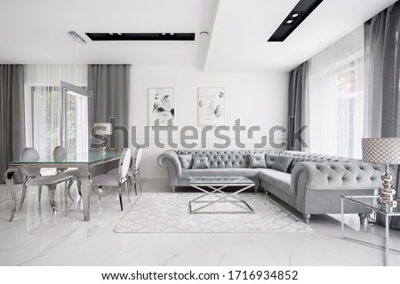 Glamour style white and gray living room with quilted corner sofa and elegant glass coffee and dining table Royalty-Free Stock Photo #1716934852
