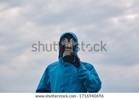 Closeup portrait of chemical scientist or ecologist posing outdoor, dresses blue uniform and respirator, scientist explores surroundings, calls on to protect our environmental. Ecology concept. #1716940696