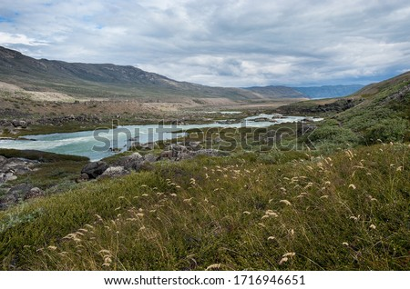 Cloudy wether in the tundra land. Expedition to Greenland. Summer in the Arctic circle. Severe landscape of the polar stream river.