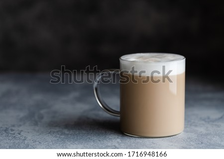 A cup of cafe latte, cafe au lait or chai latte. The photo shows a beige or light brown drink with a white foam on top. The drink is in a glass mug, and is on a dark gray background with copy space.  #1716948166