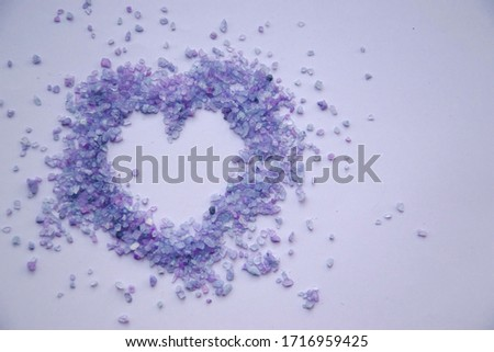 Close up picture of violet heart on light lavender background. Decorative sea salt with purple shade. Small crystals of salt. Top view, copy space concept. Greeting card on valentine,wedding, engagemt