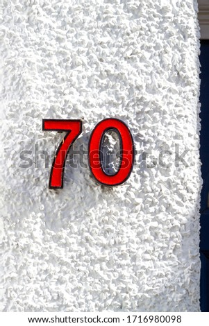 House number 70 in red on a white wall