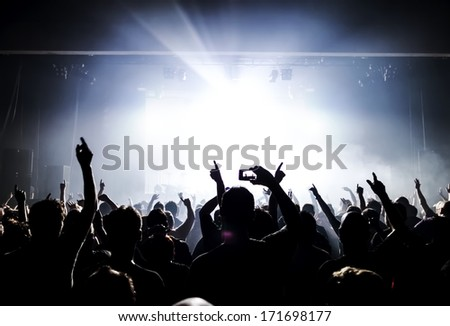silhouettes of concert crowd in front of bright stage lights #171698177
