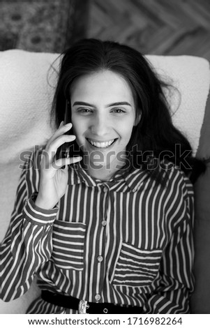 Fashionable young Caucasian woman laying on sofa at home holding mobile phone and talking with friend. She is smiling and enjoying conversation. Black and white photo.