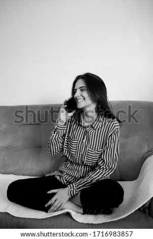 Fashionable young Caucasian woman sitting on sofa at home holding mobile phone and talking with friend. She is smiling and enjoying conversation. Black and white photo.