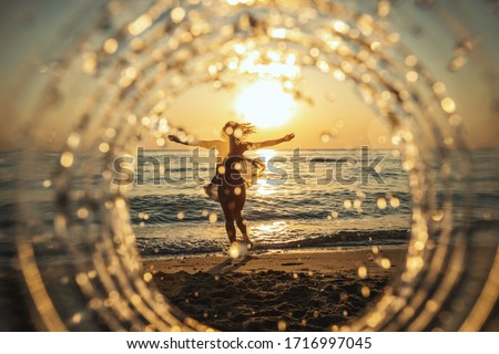 A beautiful creative composition of a sea landscape shot through a circle focus showing a young woman who is having fun on the beach in sunset. Royalty-Free Stock Photo #1716997045