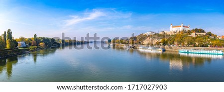 Panoramic scenery view of Danube river in Bratislava, Slovakia. Bratislava Castle building on the right. Sunny autumn day Royalty-Free Stock Photo #1717027903