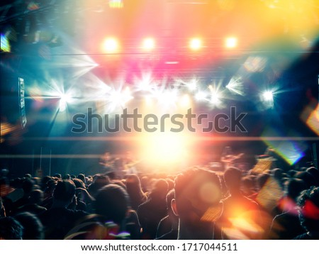 Music festival shot inside a concert hall with people clapping a band on the stage for a live show. Royalty-Free Stock Photo #1717044511