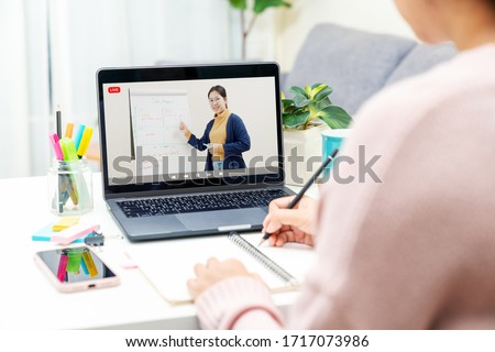 Back rear view of young asian girl sit on desk and learn at home living room in concept of romote learning, virtual online, self isolated quarantine lifestyle in asia. Teaching video call on computer. Royalty-Free Stock Photo #1717073986