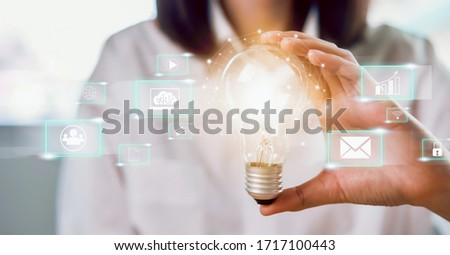 Woman hand holding light bulb with innovative and creativity are keys to success and show technology icon social media.