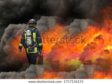 fireman using extinguisher to fighting with fire flame in an emergency situation, under danger situation all firemen wearing fire fighter suit for safety. Royalty-Free Stock Photo #1717136155