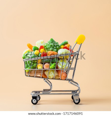 Frozen vegetables assorted in toy shopping cart on cream background. Full of assorted frozen vegetables food shop trolley at beige or yellow backdrop. Minimalistic concept. #1717146091