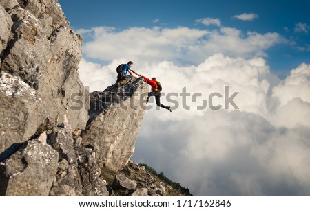 Male climber reaching out to help his friend get over the cliffs edge  #1717162846