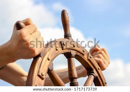 Steering hand wheel ship on sky background, hand hold hand wheel #1717173739