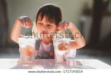 Easy science experiment at home to learn about the density of salt water effect to floating and sinking of the eggs, concept of child education and learning through play activity at home. Royalty-Free Stock Photo #1717193014