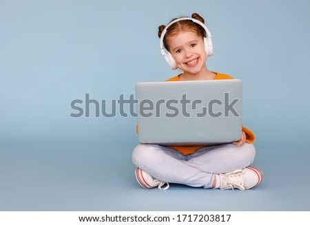 Full body positive little girl in headphones smiling and watching cartoon on modern laptop while sitting crossed legged on blue background