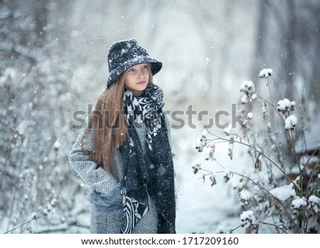 Winter portrait of a child on a background of snowy bushes and trees. Image with selective focus and with toning.