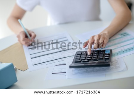 Calculation process. Close-up of female hands pressing buttons on calculator, holding pen #1717216384