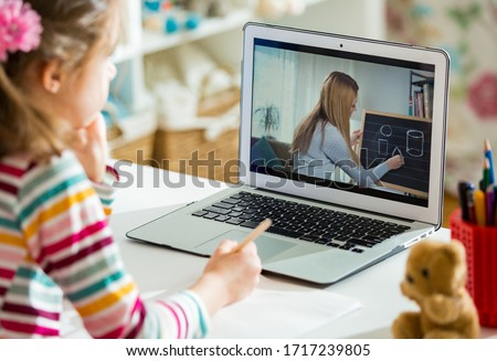 Young female distance teacher having video conference call with pupil using webcam. Online education and e-learning concept. Home quarantine distance learning and working from home. #1717239805