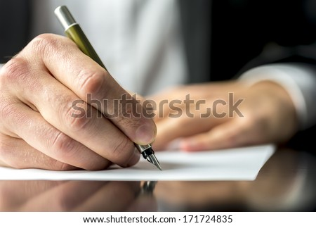 Close up of the hands of a businessman in a suit signing or writing a document on a sheet of white paper using a nibbed fountain pen #171724835