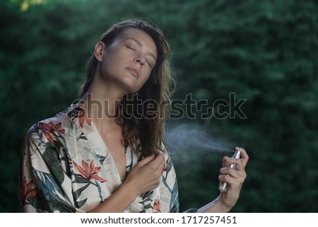 Woman refreshing with thermal water against summer heatwave. Woman spraying body or hair mist, summertime skincare and haircare concept. Royalty-Free Stock Photo #1717257451
