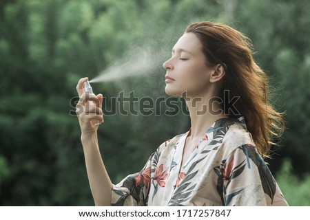 Woman spraying facial mist on her face, summertime skincare concept Royalty-Free Stock Photo #1717257847