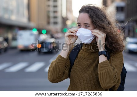 Caucasian woman out and about in the city streets during the day, putting on a face mask against covid19 coronavirus #1717265836