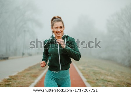 Close photo of fit sportswoman with beautiful smile while jogging outside on cold and foggy morning.