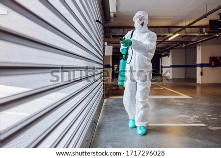 Full length of worker in sterile protective suit and mask sterilizing door of a garage from corona virus / covid-19. #1717296028