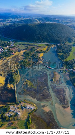 Aerial View of Marisma de Joyel Wetlands around Isla village in Arnuero  Municipality within Marismas de Santona, Victoria y Joyel Natural Park, a Ramsar Site of Cantabria in Spain of Europe #1717337911