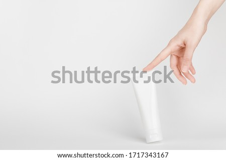 Female hand touching flacon for cream. Container for body lotion, toiletry. Tube for professional care products. Skincare and advertising concept. Mockup style and copy space. Isolated on gray Royalty-Free Stock Photo #1717343167