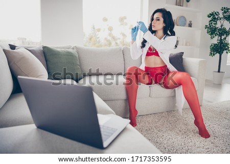 Photo of hot lady work home sit couch spread legs online notebook chat undress play naughty hot lover nurse role hold syringe preparing injection take off lab coat look screen wear red bikini indoors