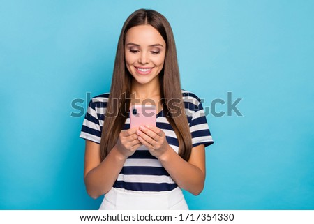 Photo of beautiful cheerful lady hold telephone hands reading email check blog comments reactions followers wear striped t-shirt white skirt isolated blue color background #1717354330
